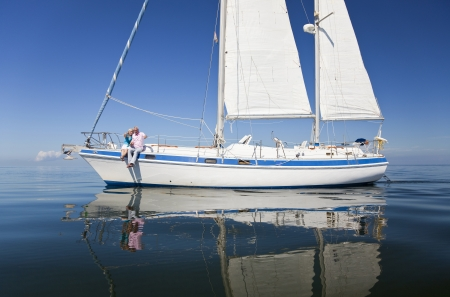 A happy senior couple having fun sitting on the deck of a sail boat on a calm blue sea photo