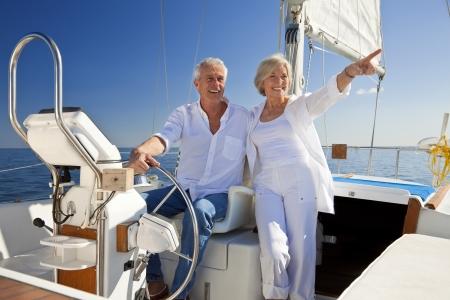 timon de barco: Un par mayor feliz que se sienta al volante de un barco de vela en un mar azul en calma
