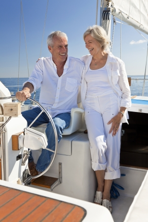 happy rich woman: A happy senior couple sitting at the wheel of a sail boat on a calm blue sea