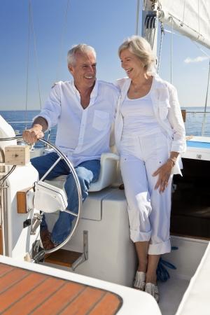 rijke vrouw: Een gelukkige senior paar zit aan het stuur van een zeilboot op een kalme blauwe zee Stockfoto