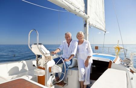 timon barco: Un par mayor feliz que se sienta al volante de un barco de vela en un mar azul en calma