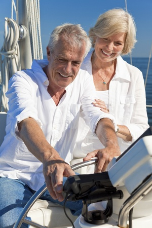 A happy senior couple sitting at the wheel of a sail boat on a calm blue sea using a satelite navigation GPS system photo