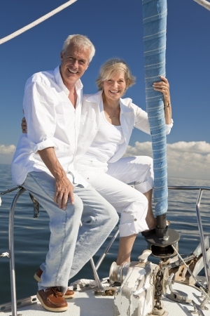 A happy senior couple sitting at the bow of a sail boat on a calm blue sea Banco de Imagens