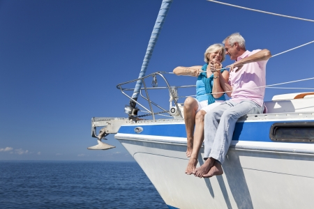 sail boat: A happy senior couple holding hands, laughing while sitting on a sail boat on a calm blue sea