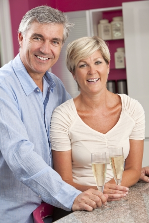 An middle aged happy, smiling man and woman married couple drinking glasses of Champagne in a kitchen at home photo