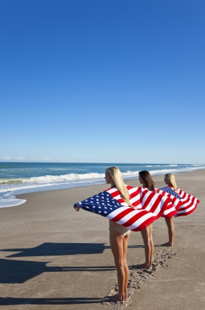 Three beautiful young women wearing bikinis and wrapped in American flags on a sunny beach photo