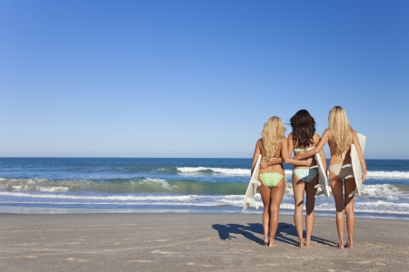 surfers: Rear view of three Beautiful young women surfer girls in bikinis with white surfbords at a beach Stock Photo
