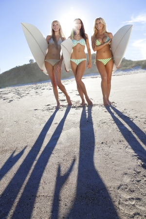 surfers: Three beautiful young women surfer girls in bikinis with white surfbords at a beach Stock Photo