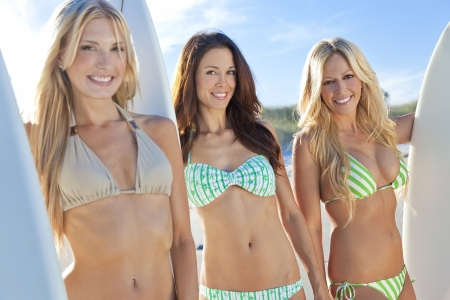 Three beautiful young women surfer girls in bikinis with white surfbords at a beach photo