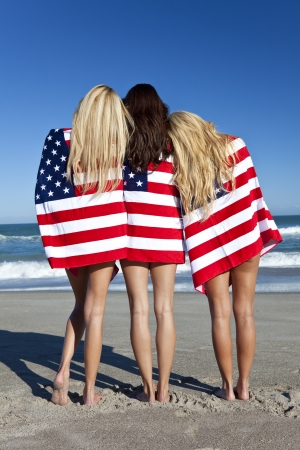 american sexy: Three beautiful young women wearing bikinis and wrapped in American flags on a sunny beach Stock Photo