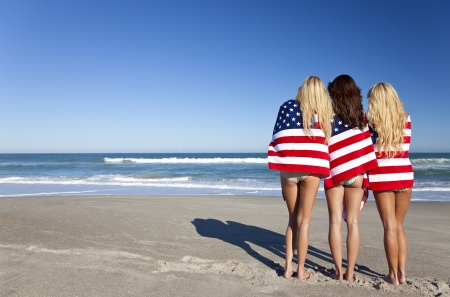 Three beautiful young women wearing bikinis and wrapped in American flags on a sunny beach Stock Photo