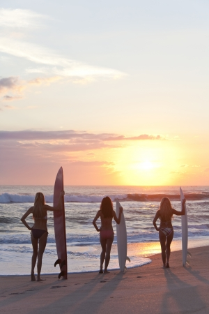 perfect waves: Rear view of three beautiful young woman surfer girls in bikinis with surfboard at a beach during sunset or sunrise