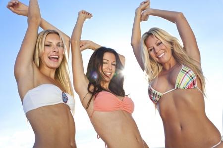 Drei schöne junge Frauen oder Mädchen in Bikinis tanzen auf einem sonnigen Strand mit Hintergrundbeleuchtung Standard-Bild - 22111108