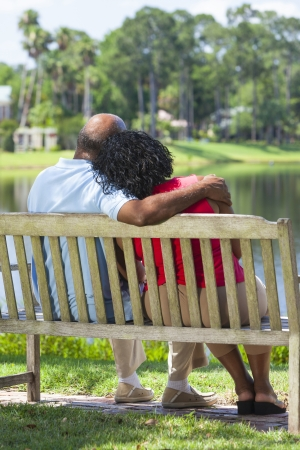 elderly couples: Rear view of a happy romantic senior African American couple sitting on a park bench embracing looking at a lake