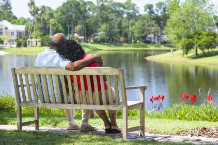 man rear view: Rear view of a happy romantic senior African American couple sitting on a park bench embracing looking at a lake