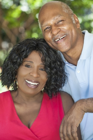 aging american: A happy senior African American man and woman couple in their sixties outside together smiling.