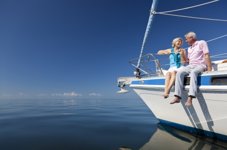 A happy senior couple sitting on the front of a sail boat on a calm blue sea photo
