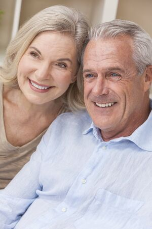 Happy senior man and woman couple sitting together at home smiling and happy photo
