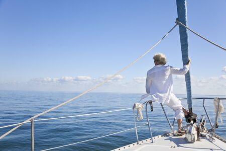 Rear view of a senior woman alone sitting on the front of a sail boat on a calm blue sea