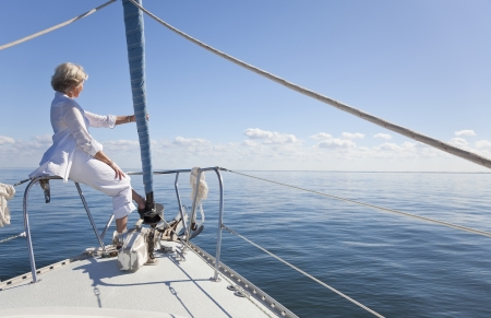 A happy senior woman sitting at the bow of a sail boat looking out to a calm blue sea Banco de Imagens
