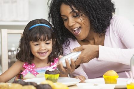 ni�os cocinando: African American madre y la hija de raza mixta que se divierten fosting hielo pasteles de taza