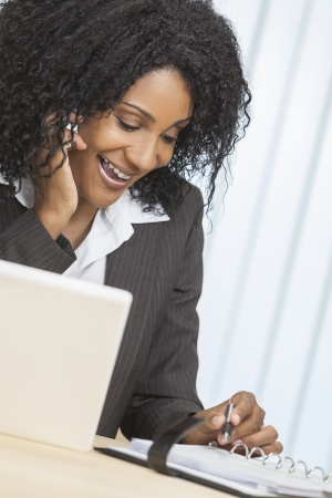Portrait of a beautiful middle aged African American woman or businesswoman using her cell phone and laptop computer in an office photo