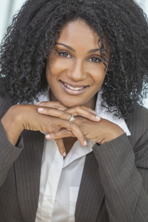sucessful: Portrait of a beautiful middle aged African American woman or businesswoman sitting relaxing & smiling