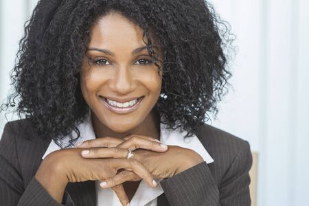 Portrait of a beautiful middle aged African American woman or businesswoman sitting relaxing & smiling photo