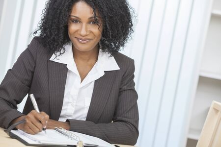 african american woman hair: Portrait of a beautiful middle aged African American woman or businesswoman sitting relaxing, writing in a diary or personal organiser & smiling