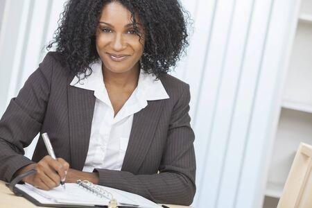 donna ricca: Ritratto di una bella mezza et� della donna dell'afroamericano o imprenditrice seduta relax, scrivendo in un diario o organizzatore personale e sorridente Archivio Fotografico