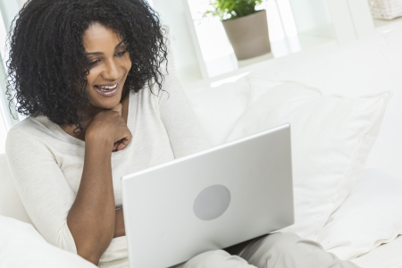 Beautiful smiling African American woman at home sitting on sofa or settee using her laptop computer. photo