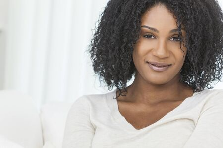 30s thirties: Portrait of a beautiful middle aged African American woman sitting at home relaxing and smiling Stock Photo