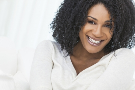 portrait of a woman: Portrait of a beautiful middle aged African American woman sitting at home relaxing smiling or laughing