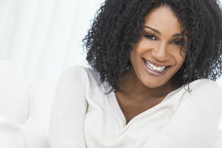 Retrato de una bella mujer de mediana edad afroamericano que se sienta en casa de relax sonre?r o re?r