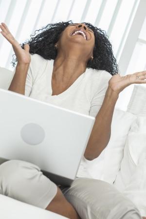 personas celebrando: African American mujer en su casa sentado en el sof� o el sof� celebrando y riendo con su ordenador port�til.