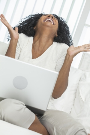 African American woman at home sitting on sofa or settee celebrating and laughing using her laptop computer.