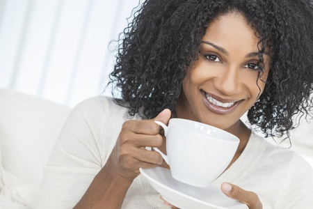 settee: Beautiful smiling African American woman at home sitting on sofa or settee drinking cup of coffee or tea