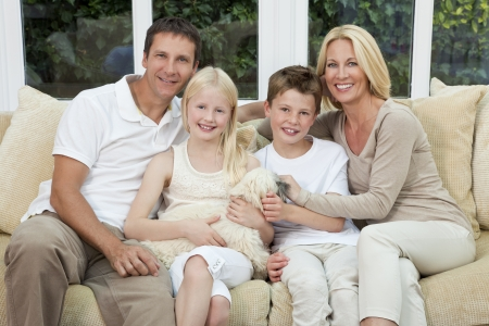 An attractive happy family of mother, father, son and daughter sitting on a sofa at home having fun with pet dog photo