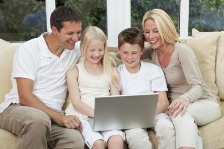 노트북이나 컴퓨터를 사용하여 가정 재미에서 소파에 앉아 어머니, 아버지, 아들과 딸의 매력적인 미소, 가족