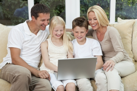 wealthy: An attractive happy, family of mother, father, son and daughter sitting on a sofa at home having fun using a laptop or computer