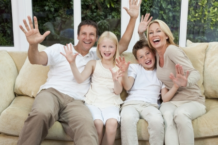 four people: An attractive happy family of mother, father, son and daughter sitting on a sofa at home having fun