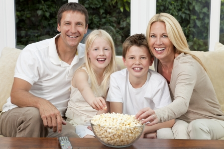 An attractive happy family of mother, father, son and daughter sitting on a sofa at home watching a film or television and eating popcorn.  photo