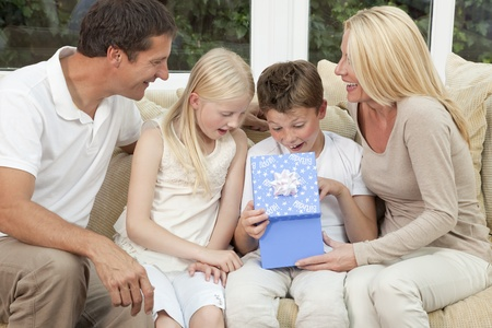 An attractive happy, family of mother, father, son and daughter sitting on a sofa at home the boy child is opening a birthday present in a blue box photo
