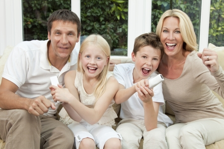 Happy family, parents, son and daughter, having fun playing video console together, the children have the remote controls, the parents are cheering. photo
