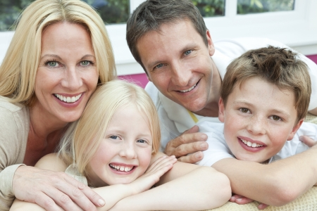 An attractive happy, family of mother, father, son and daughter sitting on a sofa at home having fun photo