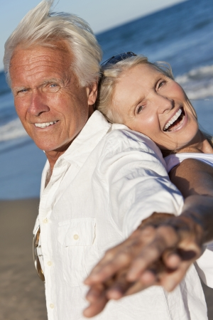 Happy senior man and woman couple dancing having fun back to back on a deserted tropical beach