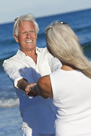 Happy senior man and woman couple dancing and holding hands on a deserted tropical beach with blue sea photo