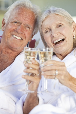 wealthy lifestyle: Happy senior man and woman couple sitting together outside in sunshine wearing white bathrobes celebrating drinking white wine Champagne