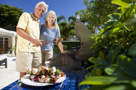 Happy senior man and woman couple outside cooking kebabs on a summer barbecue photo