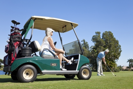 Happy senior man and woman couple together playing golf, the man is hitting a shot the woman is sitting in a golf cart